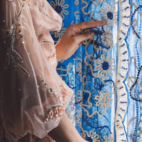 Woman wearing a unique designed transparent pink blouse from Aljamielah holding the blue curtain