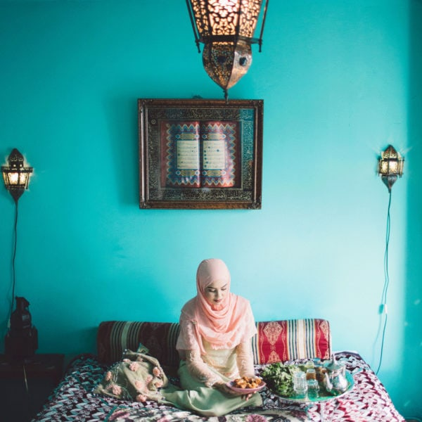 Woman sitting on a bed wearing unique designed clothes from Aljamielah holding a plate with food and next to her a tray with a teapot and tea glasses