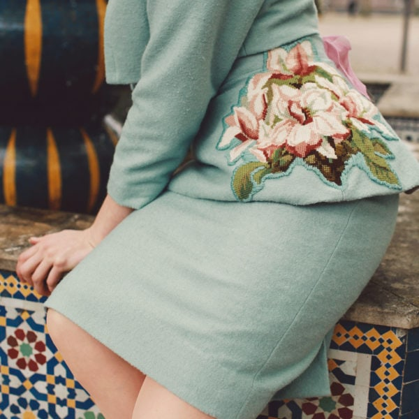Blue jacket and skirt with floral embroidery, Woman wearing a unique designed blue skirt with floral embroidery, a blue jacket sitting on a mosaic fountain