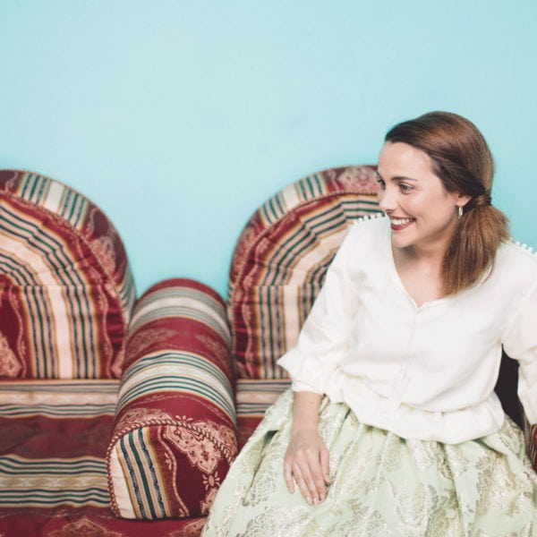 Smiling woman sitting on the couch wearing an unique designed mint green skirt and a white blouse