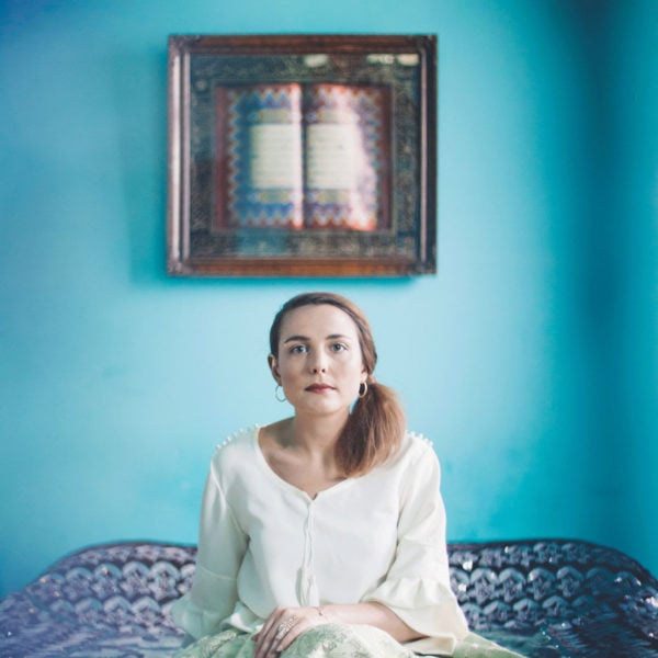 Woman wearing an unique designed mint green skirt and a white blouse sitting on a bed in a room with blue walls