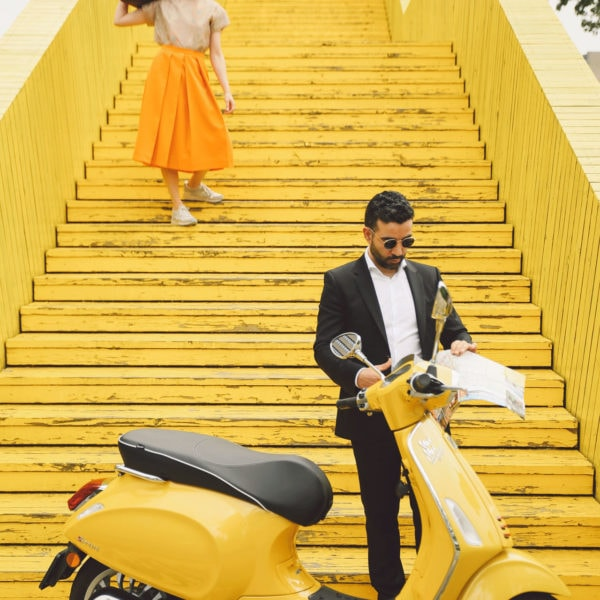 Man wearing sunglasses, a black suit and a white shirt standing behind a yellow scooter reading a paper and a woman standing on the yellow stairs wearing sunglasses, a yellow skirt, a beige blouse and a brown bag