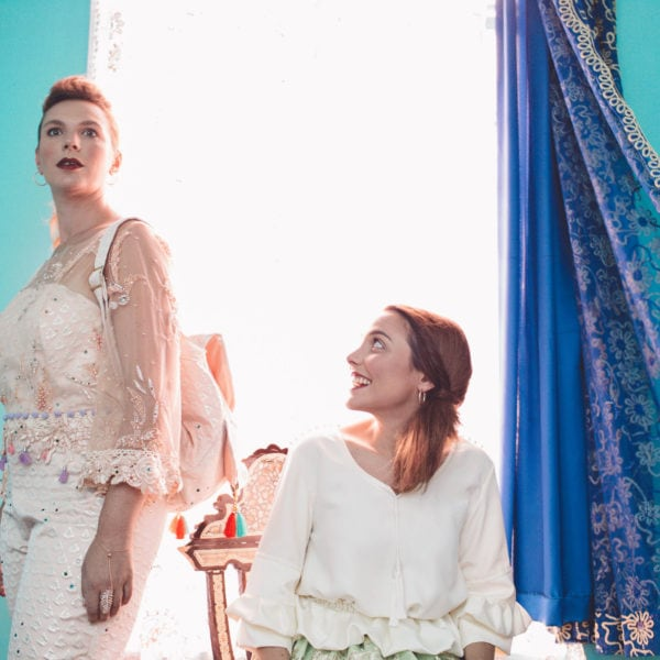 Two women wearing unique designed clothes from Aljamielah sitting and standing in a room with blue curtains and a blue wall