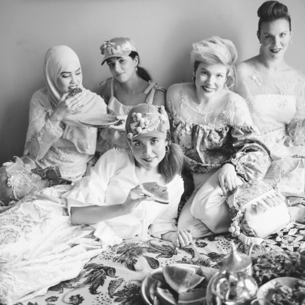 Five cultural women wearing party dresses from Aljamielah sitting on a bed