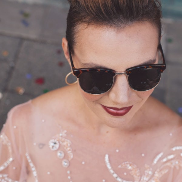 Woman with sunglasses wearing an unique designed transparent blouse from Aljamielah