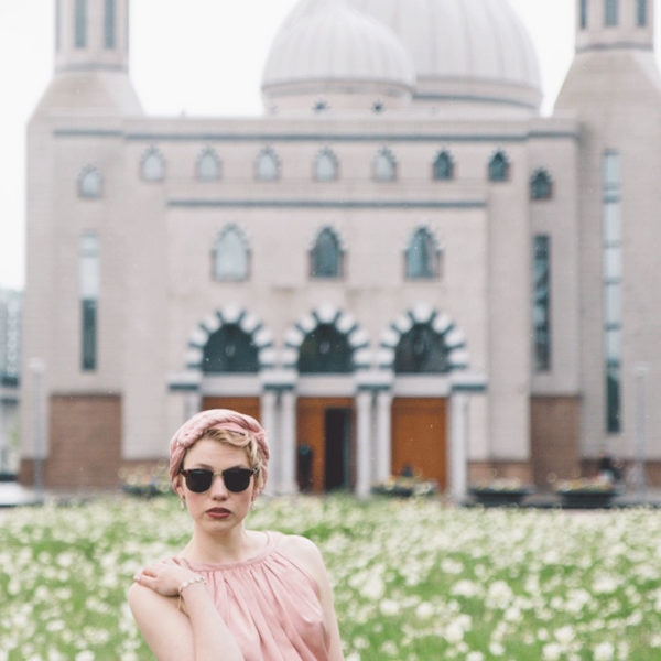 Woman standing before a mosque and white flowers wearing an unique designed pink blouse and an unique designed pants from Aljamielah