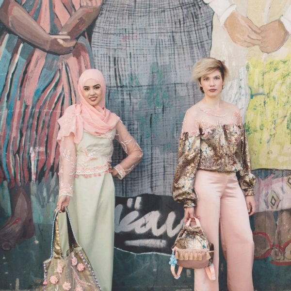 Two cultural women wearing unique designed party dresses from Aljamielah and a unique designed bag