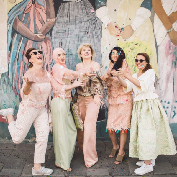 Five happy cultural women standing on the street with unique designed party dresses form Aljamielah
