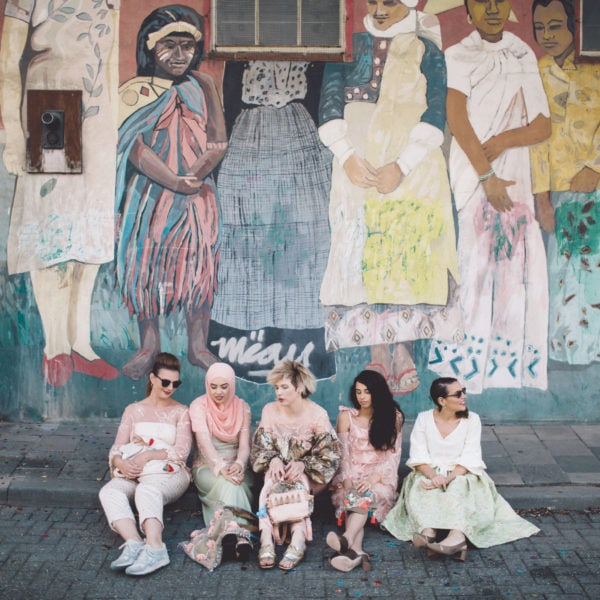 Five cultural women sitting on the ground with unique designed party dresses from Aljamielah