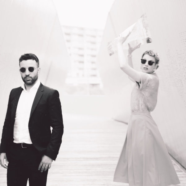 Man wearing sunglasses, a black suit and a white shirt and a woman wearing sunglasses, a skirt and a blouse holding a newspaper in the air