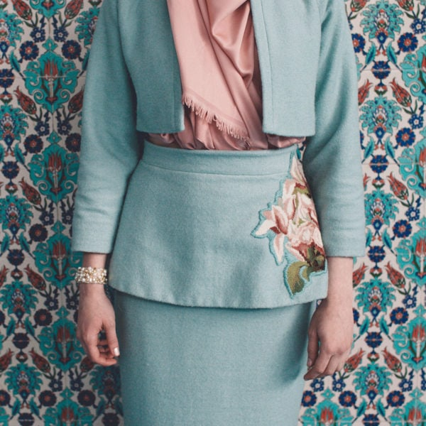 Woman wearing an unique designed blue skirt with floral embroidery, a blue jacket sitting and a pink headscarf