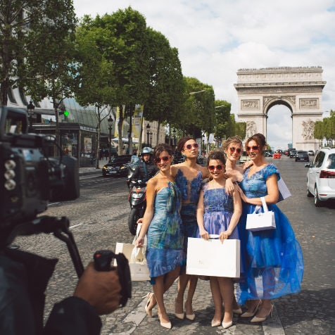 five bridesmaids posing on the street of Champs-Élysées in Paris wearing pink sunglasses and unique designed blue dresses from Truly Love Me holding shopping bags with the logo of Maison M'Elise