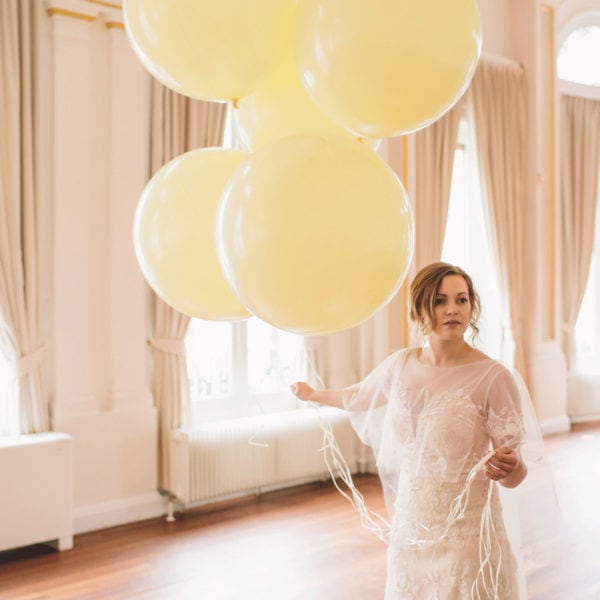Bride in an unique designed white wedding dress from Truly Love Me holding yellow balloons in a room