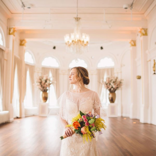 Bride is standing in the centre of a room wearing a designed wedding dress from Truly Love Me, and she is looking out the window while holding bouquet in her hands
