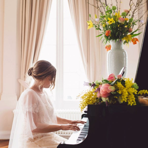Bride in an unique designed wedding dress from Truly Love Me sitting behind the piano in a hall with a bridal bouquet