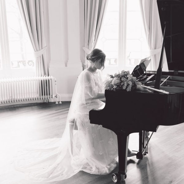 Bride in an unique designed Truly Love Me wedding dress playing behind a piano