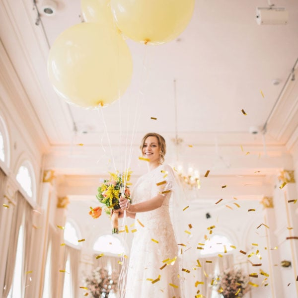 Happy bride standing in the room full of gold confetti, wearing handmade wedding gown from Truly Love Me, while holding balloons and bouquet in her hands
