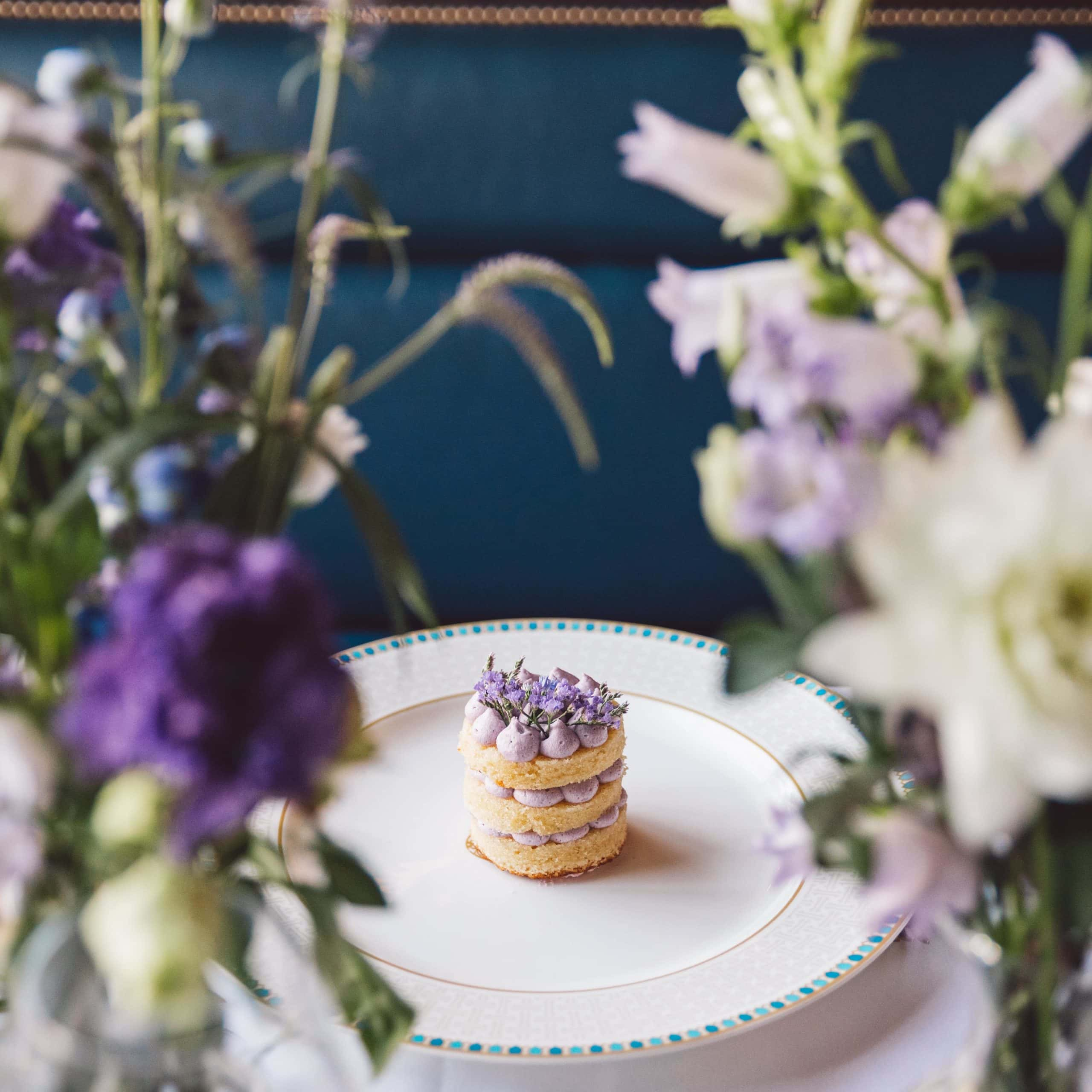 Purple whipped cream cake on a plate and a bridal bouquet