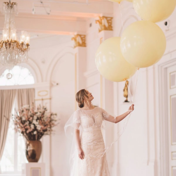 Bride in designed Truly Love Me wedding dress that looks at yellow balloons
