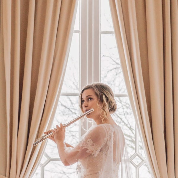 Bride in an unique designed wedding dress from Truly Love Me playing on a recorder behind the window