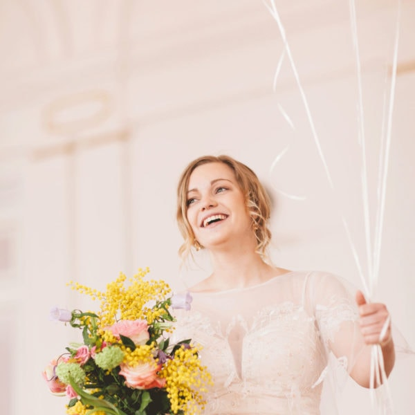 Bride wearing an unique designed wedding dress from Truly Love Me holding yellow balloons and a bridal bouquet