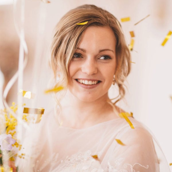 Smiling bride in an unique designed wedding dress from Truly Love Me holding a bridal bouquet