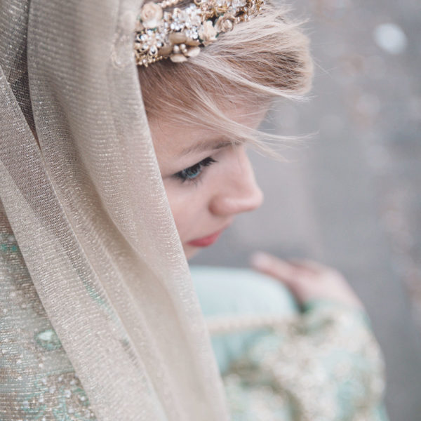 Cultural bride looking to the right side wearing an unique designed mint green Takshita, an unique designed veil and unique designed jewelry