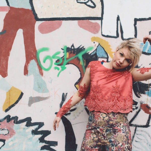 Woman wearing an unique designed red blouse and an unique designed classic high waist trousers standing before a wall with graffiti
