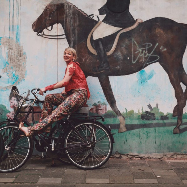 Woman sitting on a bicycle wearing a unique designed classic high waist trousers and a red blouse from Aljamielah before a wall with a horse
