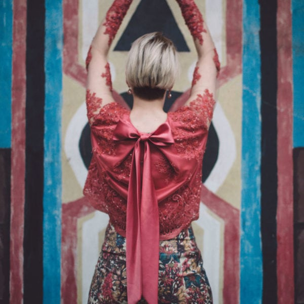 Woman wearing an unique designed classic high waist trousers and a red blouse from Aljamielah looking to a wall with different patterns holding up her hands as a triangle