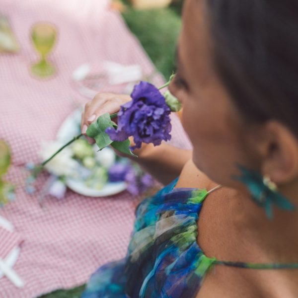 Bridesmaid wearing a blue designed bridesmaid dress from Truly Love Me holding a purple flower