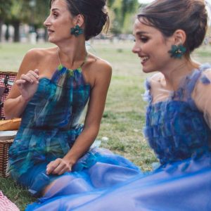 Two bridemaids wearing unique designed blue bridesmaids dresses from Truly Love Me picknicking in Paris