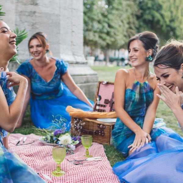 Four smiling bridesmaids wearing unique designed blue bridesmaids dresses from Truly Love Me picnicking in Paris