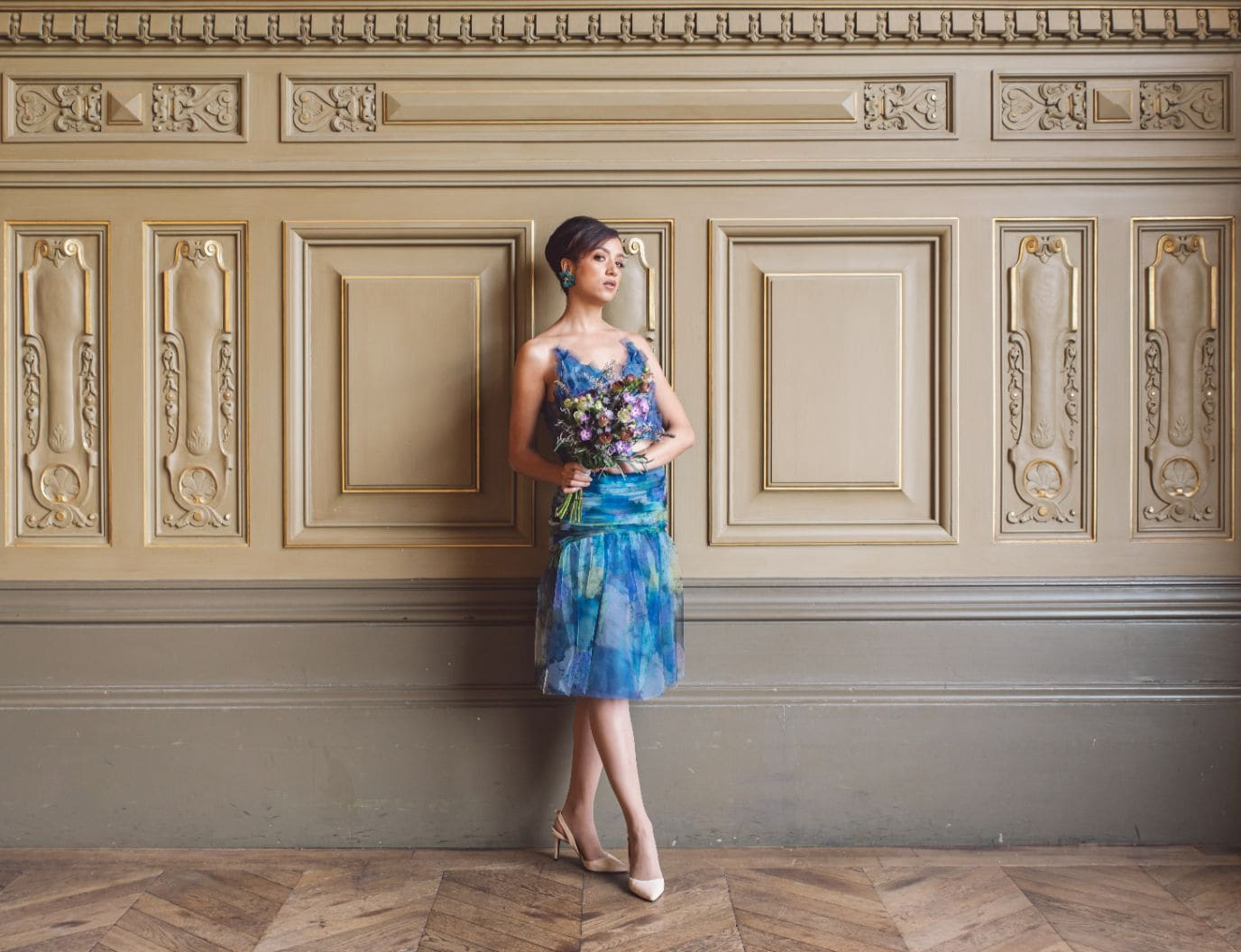 Bridesmaid holds a bridal bouquet wearing an unique designed blue dress from Truly Love Me in Paris