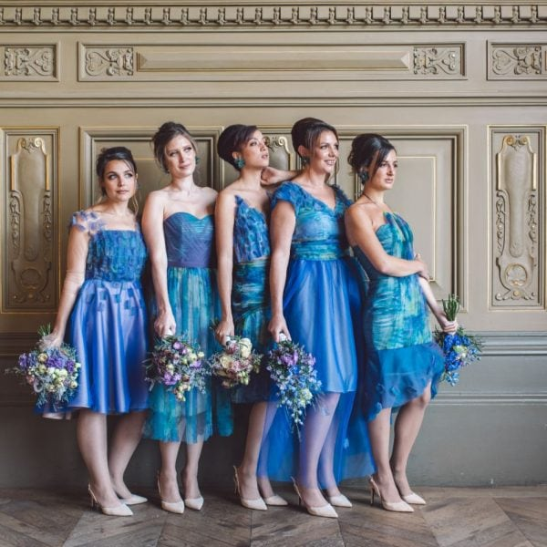 Five bridesmaids in Paris all holding a bridal bouquet wearing an unique sustainable handmade blue dresses from Truly Love Me