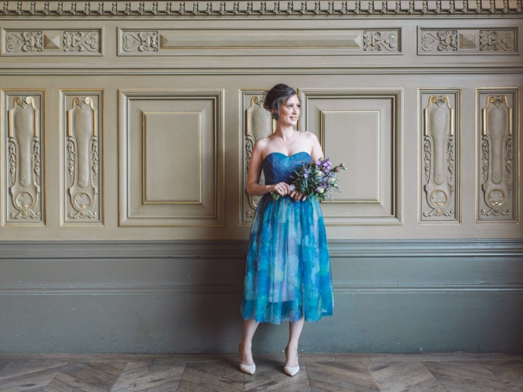 Smiling bridesmaid holds a bridal bouquet wearing an unique designed blue dress from Truly Love Me and heels in Paris