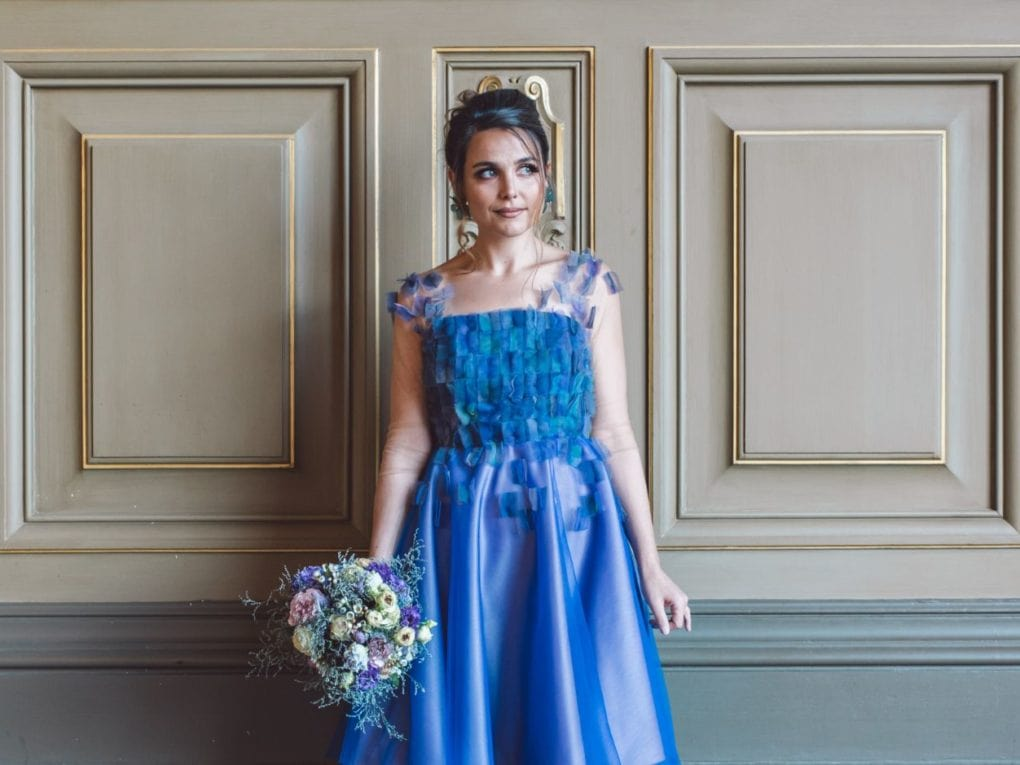 Bridesmaid holds a bridal bouquet wearing an unique designed blue dress from Truly Love Me gazing outside in Paris