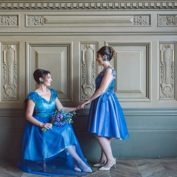 Two smiling bridesmaids holding hands wearing sustainable designed blue dresses in heels from Truly Love Me in Paris