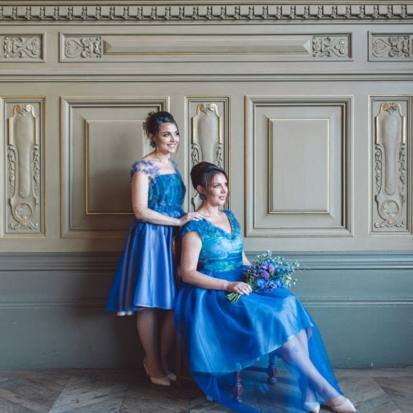 Two smiling bridesmaids looking outside in Paris wearing sustainable designed blue dresses in nude heels from Truly Love Me