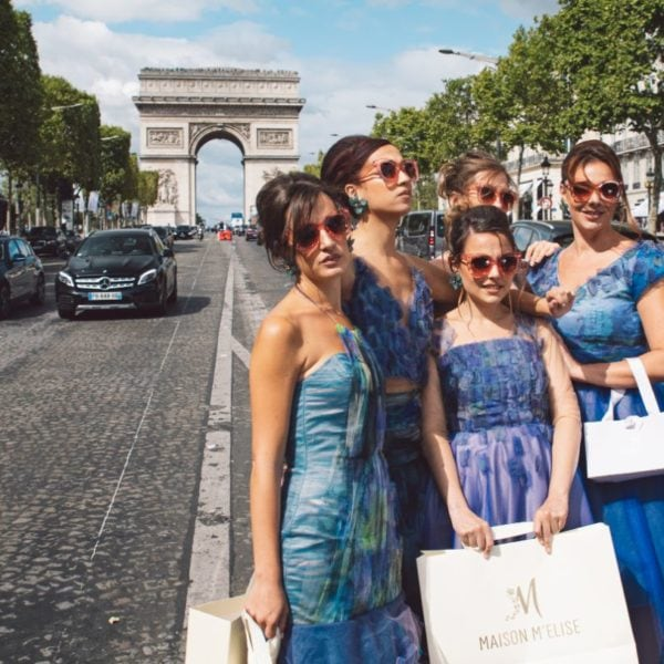 Five bridemaids wearing unique designed blue bridesmaids dresses from Truly Love Me standing on the street before L'Arc de Triomphe in Paris
