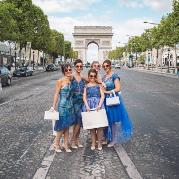 Five bridesmaids wearing unique designed blue bridesmaids dresses from Truly Love Me standing on the street before L'Arc de Triomphe in Paris