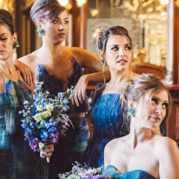 Four bridesmaids wearing unique designed blue bridesmaids dresses from Truly Love Me looking to the left side in Paris