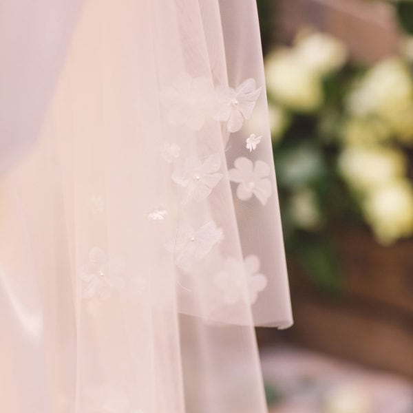 A sustainable satin bridal veil embroidered with blossoms designed by Maison M'Elise