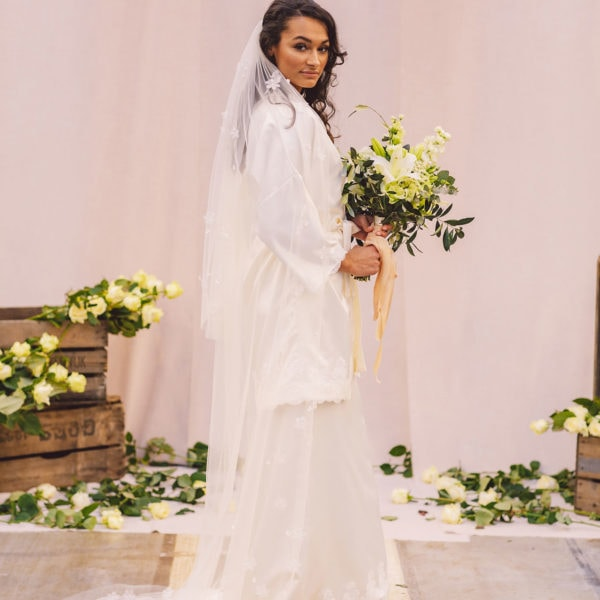 Cultural bride standing in front of beige cloths holding a bridal bouquet is wearing sustainable white satin kimono, bridal spanish lace veil, and white satin nightgown designed by Maison M'Elise