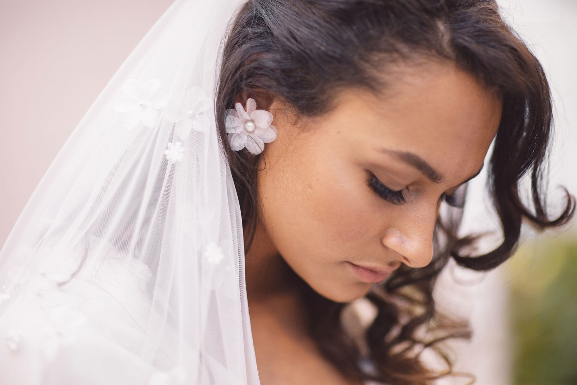 Cultural bride wearing flower earrings and handmade bridal spanish lace veil by Maison M'Elise