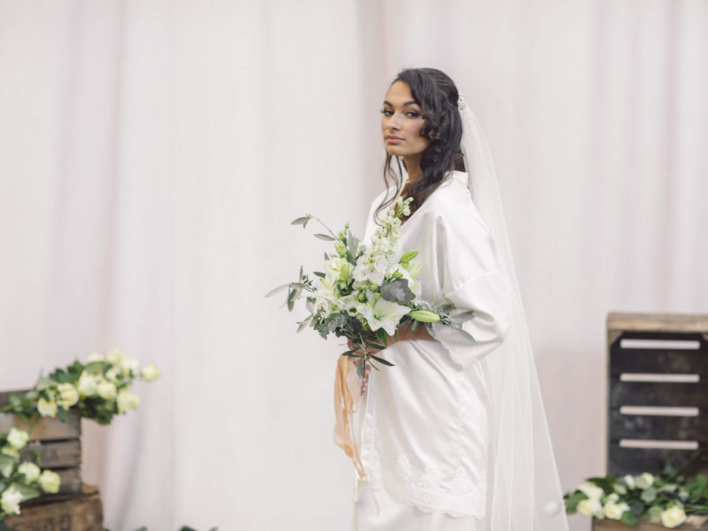 Cultural bride standing in front of beige cloths holding a bridal bouquet is wearing sustainable white satin kimono, bridal veil, and white satin nightgown designed by Maison M'Elise