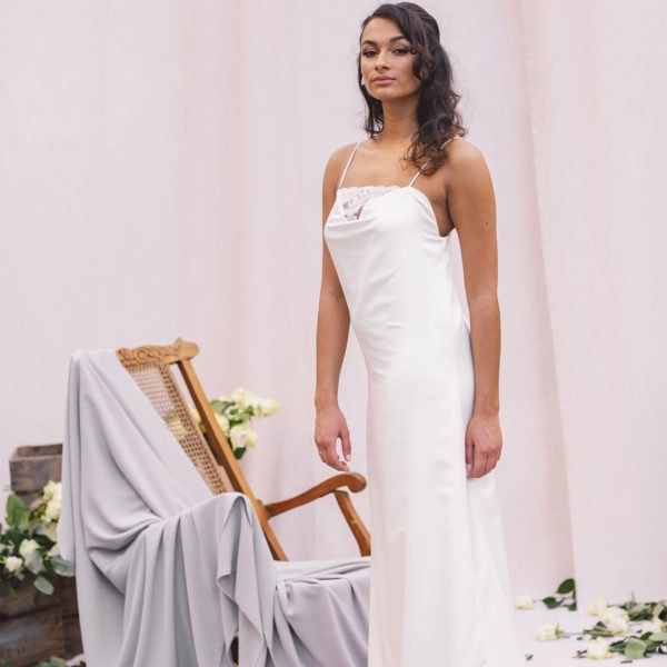 Cultural woman standing in front of beige cloths and wooden chair is wearing a sustainable handmade white satin nightgown by Maison M'Elise