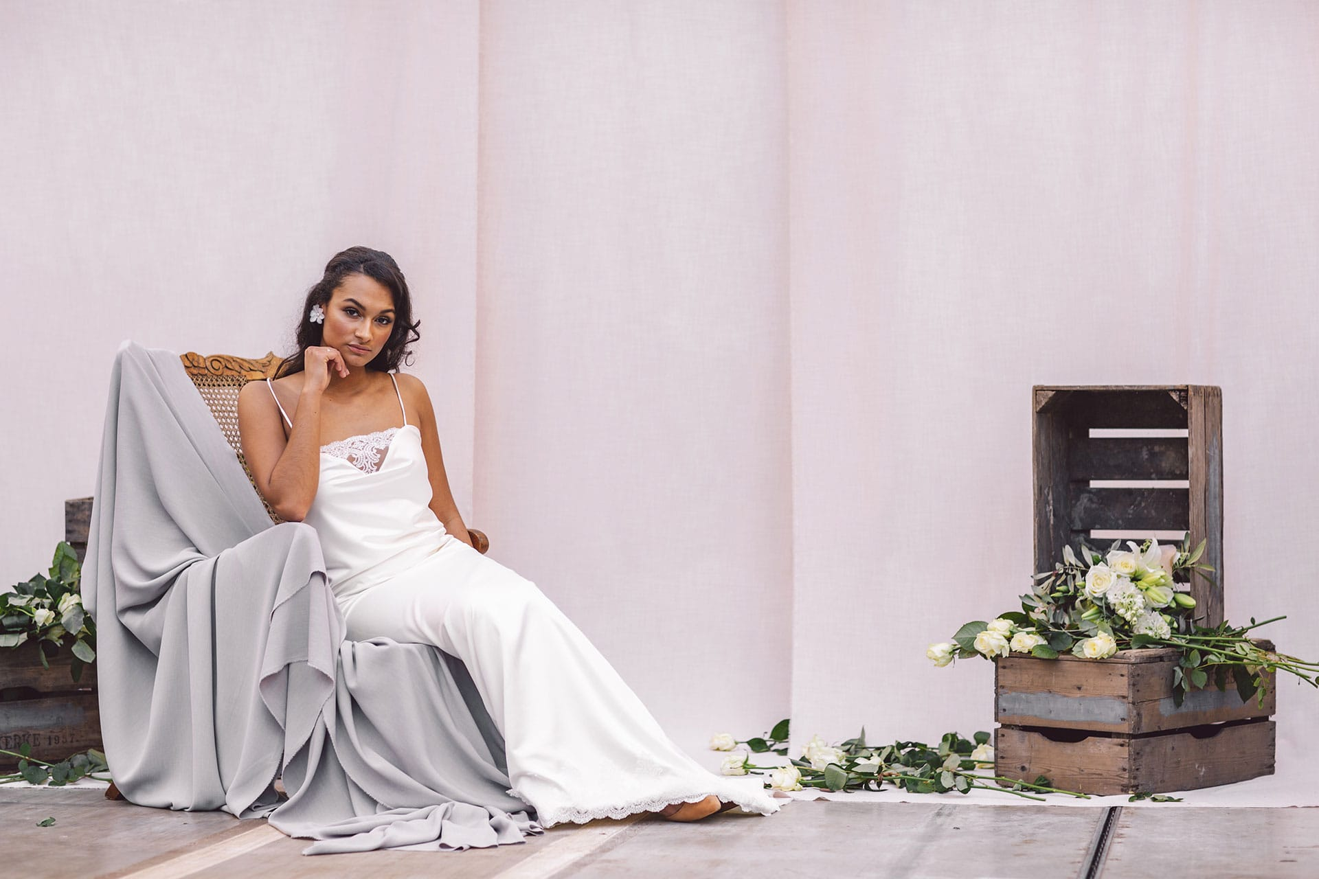 Cultural woman seated on a wooden chair in front of beige cloths with wooden boxes is wearing a white satin nightgown by Maison M'Elise