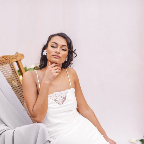 Cultural woman seated on a wooden chair with hand under her chin is wearing an unique designed white satin nightgown by Maison M'Elise
