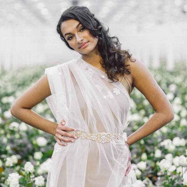 cultural woman standing in a room full of white roses wearing an unique handmade gold crystal belt from Maison M'Elise